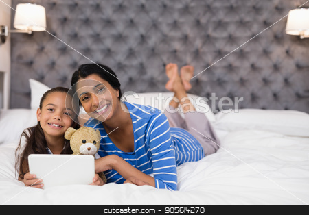 Smiling mother and daughter using digital tablet while lying on bed at home stock photo, Portrait of smiling mother and daughter using digital tablet while lying on bed at home by Wavebreak Media