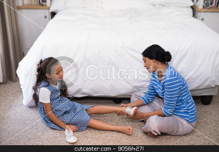 High angle view of mother helping daughter to wear shoe stock photo, High angle view of mother helping daughter to wear shoe at home by Wavebreak Media
