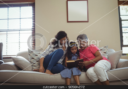 Mother and daughter reading book in living room stock photo, Mother and daughter reading book in living room at home by Wavebreak Media