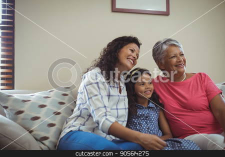 Happy family sitting on sofa in living room stock photo, Happy family sitting on sofa in living room at home by Wavebreak Media