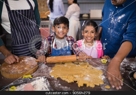 Portrait of smiling siblings preparing food with parents in kitchen stock photo, Portrait of smiling siblings preparing food with parents in kitchen at home by Wavebreak Media