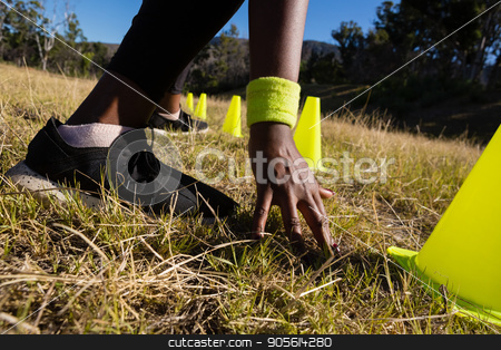 Woman touching the finish line while running through training cones stock photo, Woman touching the finish line while running through training cones on a sunny day by Wavebreak Media