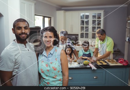 Couple smiling at camera while family members preparing dessert in background stock photo, Couple smiling at camera while family members preparing dessert in background at home by Wavebreak Media