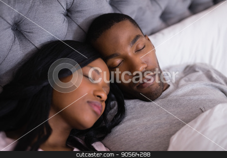High angle view of couple sleeping together on bed stock photo, High angle view of couple sleeping together on bed at home by Wavebreak Media