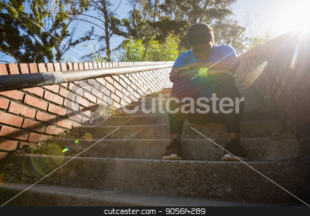 Upset woman sitting on staircase in the boot camp stock photo, Upset woman sitting on staircase in the boot camp on a sunny day by Wavebreak Media