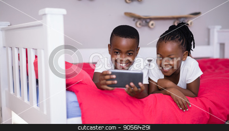 Siblings using mobile phone while lying on bed at home stock photo, Happy siblings using mobile phone while lying on bed at home by Wavebreak Media