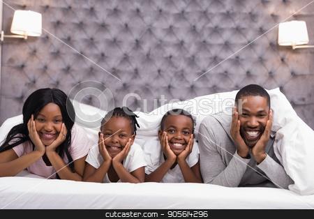 Portrait of smiling family lying together under blanket on bed stock photo, Portrait of smiling family lying together under blanket on bed at home by Wavebreak Media