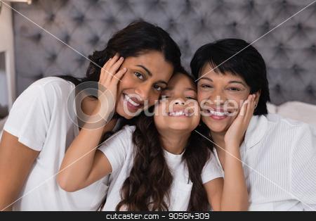 Portrait of smiling multi-generation embracing on bed stock photo, Portrait of smiling multi-generation embracing on bed at home by Wavebreak Media