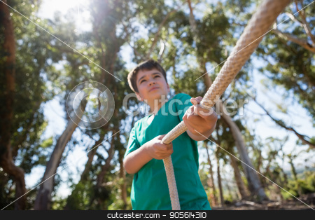Boy practicing tug of war during obstacle course training stock photo, Boy practicing tug of war during obstacle course training in the boot camp by Wavebreak Media