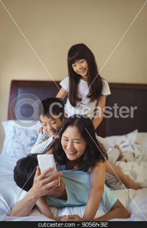 Happy family using mobile phone in the bed room stock photo, Happy family using mobile phone in the bed room at home by Wavebreak Media