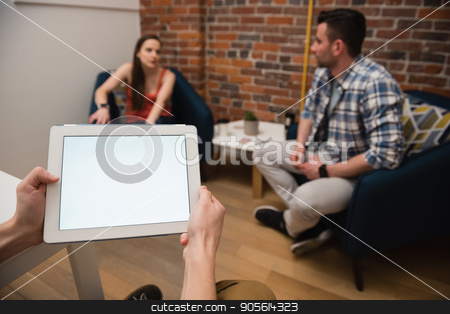 Executive using digital tablet and colleagues discussing in background stock photo, Executive using digital tablet and colleagues discussing in background at office by Wavebreak Media