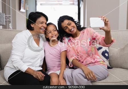 Happy multi-generation family taking selfie together at home stock photo, Happy multi-generation family taking selfie while sitting together at home by Wavebreak Media