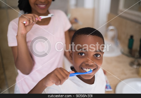 Boy with mother brushing teeth at home stock photo, Portrait of boy with mother brushing teeth at home by Wavebreak Media