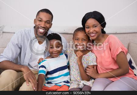 Happy family sitting on sofa at home stock photo, Portrait of happy family sitting on sofa at home by Wavebreak Media
