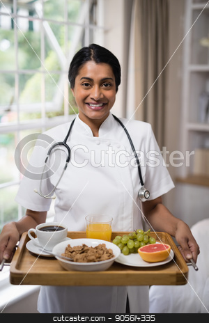Smiling nurse holding breakfast tray at home stock photo, Portrait of smiling nurse holding breakfast tray at home by Wavebreak Media