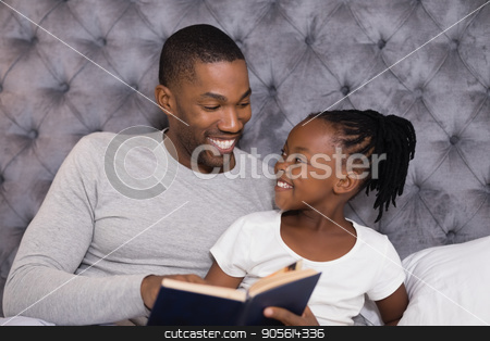 Happy man with daughter reading book on bed stock photo, Happy man with daughter reading book while sitting on bed at home by Wavebreak Media