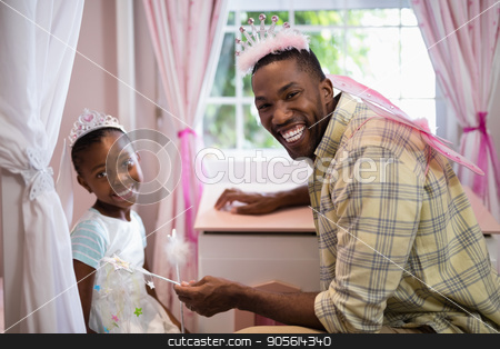 Happy father and daughter wearing costume wings at home stock photo, Portrait of happy father and daughter wearing costume wings at home by Wavebreak Media