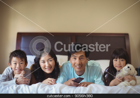 Happy family watching television in the bed room stock photo, Happy family watching television in the bed room at home by Wavebreak Media