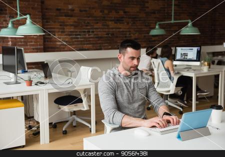 Male executive using digital tablet at desk stock photo, Male executive using digital tablet at desk in office by Wavebreak Media