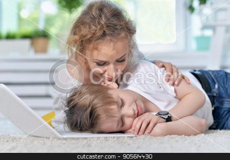 Mother awaken little son stock photo, Mother awaken little son who sleeping on floor near laptop by Ruslan Huzau