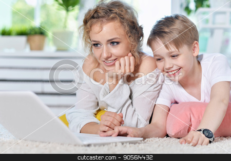 Mother and son looking at modern laptop stock photo, Mother and son lying on floor and looking at modern laptop by Ruslan Huzau