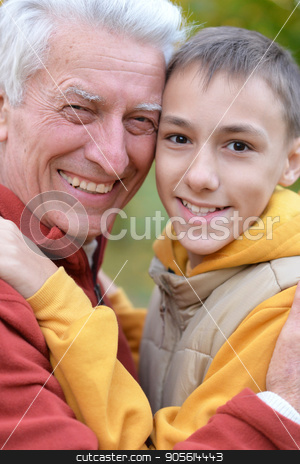 Smiling grandfather and grandson  stock photo, Close up portrait of smiling grandfather and grandson outdoors by Ruslan Huzau