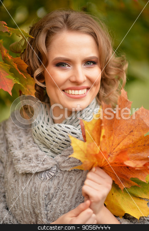 Young woman resting in park stock photo, Beautiful young woman resting in autumnal park by Ruslan Huzau