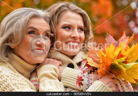 Senior woman with daughter resting  stock photo, Senior woman with daughter resting in autumnal park by Ruslan Huzau