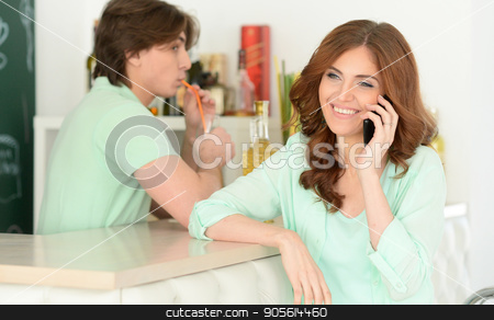 Young woman talking on phone stock photo, Young woman talking on phone while man drinking on background by Ruslan Huzau