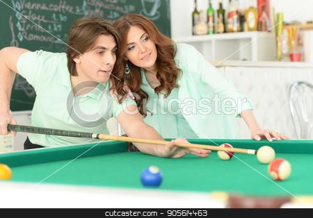 young couple playing billiard stock photo, Portrait of happy young couple playing billiard by Ruslan Huzau