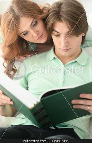 Young couple reading book stock photo, Portrait of young couple reading book together by Ruslan Huzau
