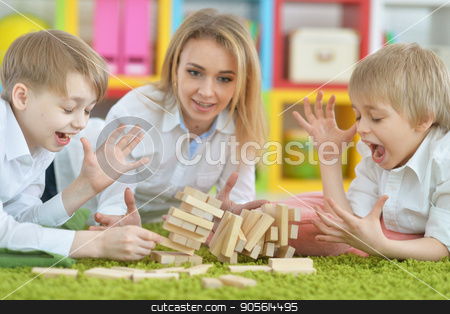 young mother and two sons playing stock photo, Beautiful young mother and two sons playing with wooden blocks by Ruslan Huzau