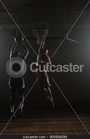 Basketball player shooting a basketball with a defender stock photo, Basketball player shooting while a defender trying to block him in a gymnasium by Wavebreak Media