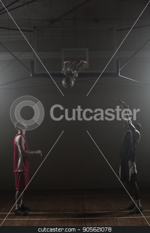 Two basketball player in a gymnasium with one scoring a shoot stock photo, Two basketball player in a gymnasium with one scoring a shoot against a black background by Wavebreak Media
