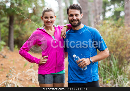Athletic couple standing together in forest stock photo, Portrait of athletic couple standing together in forest by Wavebreak Media