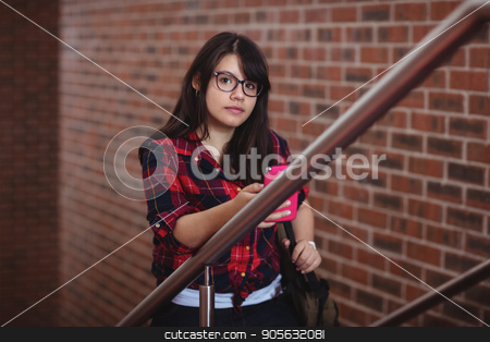 Female student walking on staircase stock photo, Portrait of female student walking on staircase in college by Wavebreak Media