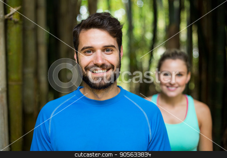 Couple standing in forest stock photo, Portrait of athletic couple standing in forest by Wavebreak Media