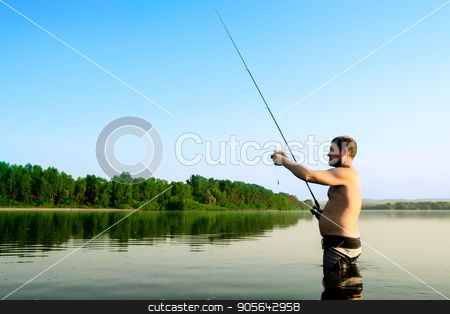 fisherman fishing in a calm river in the morning. Man in fishing gear stending in a river and throws a fishing pole stock photo, fisherman fishing in a calm river in the morning. Man in fishing gear stending in a river and throws a fishing pole. by Alexander