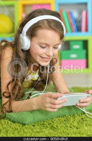 Cute little girl with headphones stock photo, Cute little girl with smartphone and headphones by Ruslan Huzau