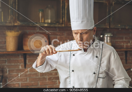 Mature man professional chef cooking meal indoors stock photo, Mature male professional chef cooking meal indoors taste food by Dmytro Sidelnikov