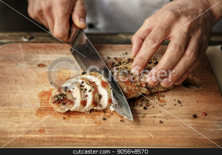 Mature man professional chef cooking meal indoors stock photo, Mature male professional chef cooking meal indoors cutting meat by Dmytro Sidelnikov