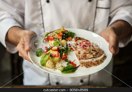 Mature man professional chef cooking meal indoors stock photo, Mature male professional chef cooking meal indoors finished by Dmytro Sidelnikov