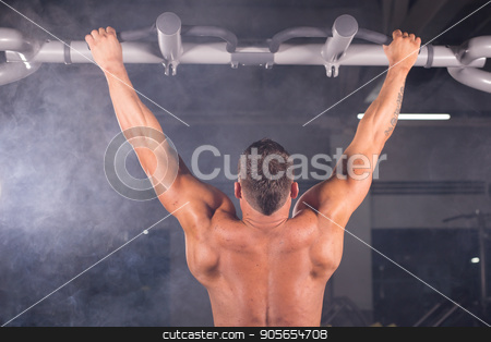 Athlete muscular fitness male model pulling up on horizontal bar in a gym. stock photo, Athlete muscular fitness male model pulling up on horizontal bar in a gym by Satura86