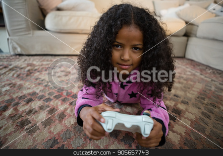 Girl playing video game in the living room at home stock photo, Portrait of girl playing video game in the living room at home by Wavebreak Media