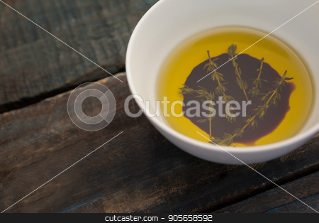High angle view of herbs in olive oil stock photo, High angle view of herbs in olive oil on wooden table by Wavebreak Media