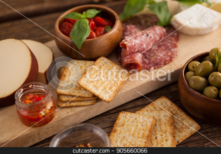 Crackers with meat and olives stock photo, Close up of crackers with meat and olives on table by Wavebreak Media