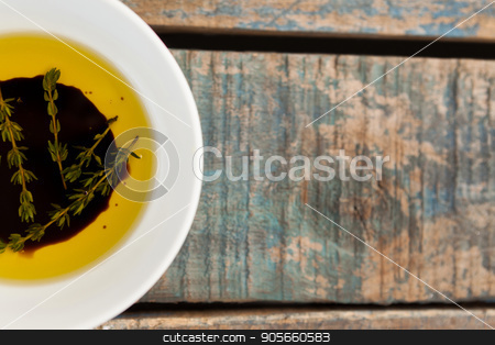 Cropped image of herbs in olive oil stock photo, Cropped image of herbs in olive oil on wooden table by Wavebreak Media