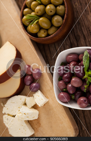 Brown and green olives by vegetable and cheese on cutting board stock photo, High angle view of Brown and green olives by vegetable and cheese on cutting board by Wavebreak Media