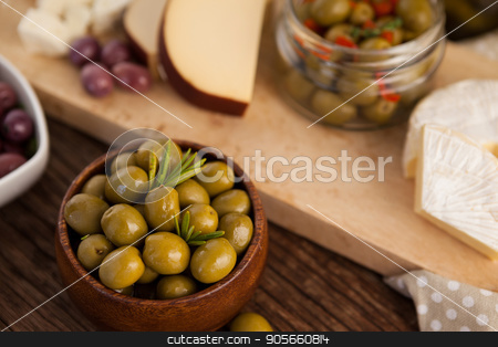 Green olives in container by cheese and vegetable stock photo, Green olives in container by cheese and vegetable on cutting b oard by Wavebreak Media