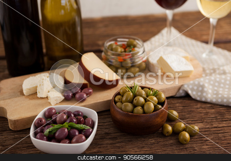 Close up of olives with cheeses and vegetable by wineglass stock photo, Close up of olives with cheeses and vegetable by wineglass on table by Wavebreak Media